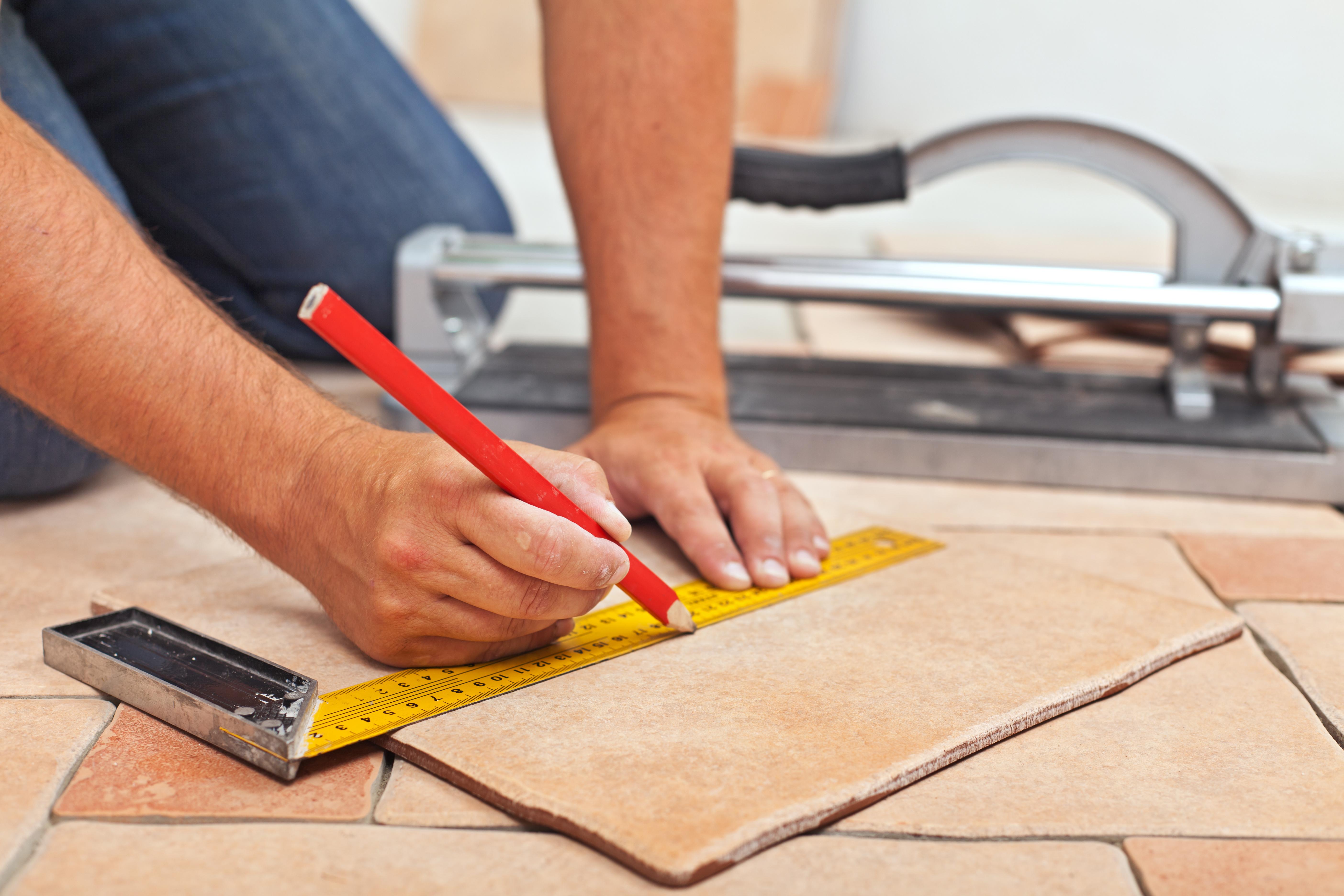 Laying ceramic floor tiles - man hands marking tile to be cut, closeup
