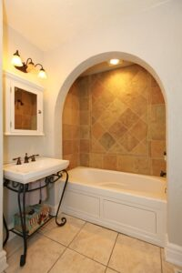 Tub with arch and stone tiles and sink natural bathroom design.
