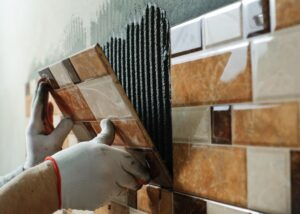 Laying Ceramic Tiles. Tiler placing ceramic wall tile in position over adhesive