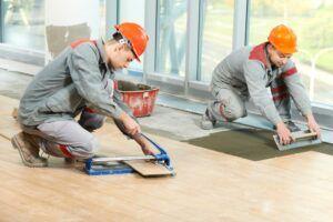 Two industrial tiler builder worker installing floor tile at repair renovation work